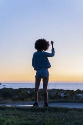 Rear view of young woman with hand in hair standing on a viewpoint at sunset, Ibiza - AFVF04403
