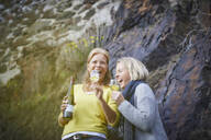 Two laughing mature women drinking wine outdoors - FMKF06044