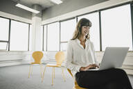 Smiling businesswoman sitting on a chair in an empty office using a laptop - KNSF06871