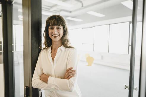 Smiling businesswoman standing in an open office door - KNSF06874
