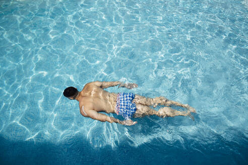 Back view of man floating in swimming pool - MIMFF00003