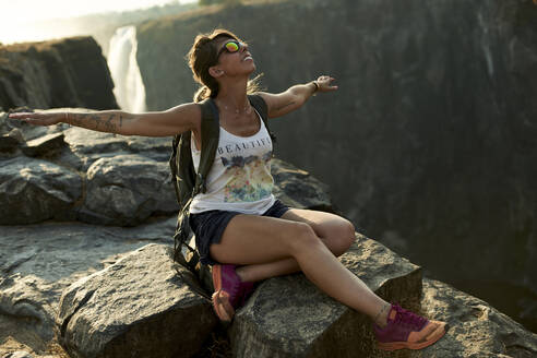 Happy woman sitting with arms open on top of a rock at Victoria Falls at sunset, Zimbabwe - VEGF01051