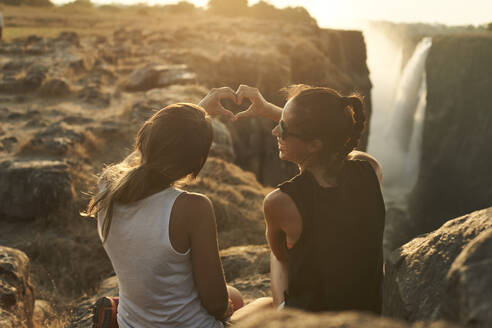 Women shaping a heart with her hands sitting in front of the Victoria Falls at sunset, Zimbabwe - VEGF01057