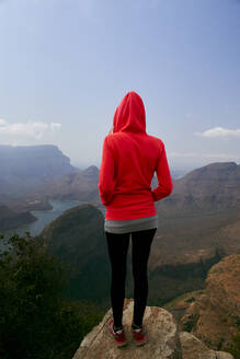 Woman standing on a rock enjoying the beautiful landscape below her, Blyde River Canyon, South Africa. - VEGF01063