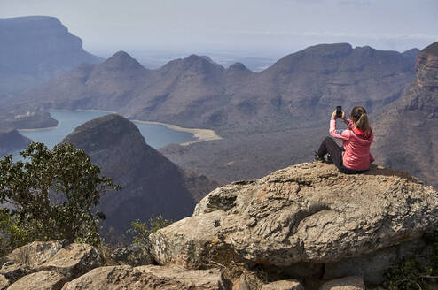Woman taking a photo with her cell phone with a beautiful landscape background, Blyde River Canyon, South Africa - VEGF01066