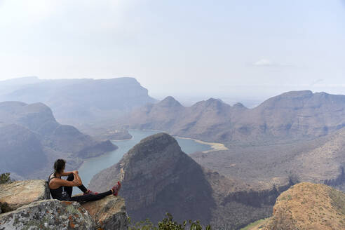 Woman sitting on a rock with beautiful landscape as background, Blyde River Canyon, South Africa - VEGF01069