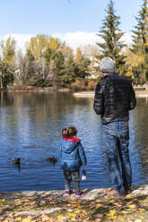 Back view of father and little daughter standing at lakeshore feeding ducks - GEMF03323