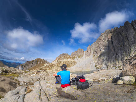 Senior man having a break from hiking in mountain landscape, Fiemme Alps, Trentino, Italy - LAF02449