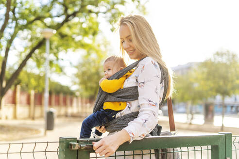 Mother carrying baby boy in a sling opening a gate - ERRF02277