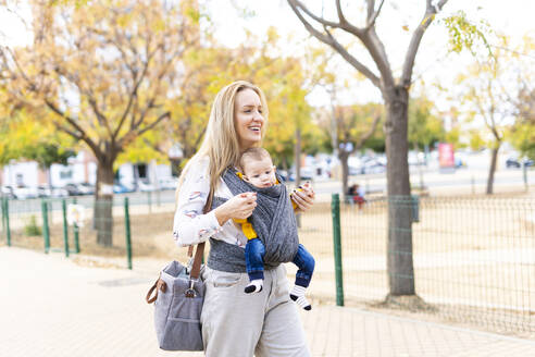 Happy mother walking with baby boy in sling outdoors - ERRF02280
