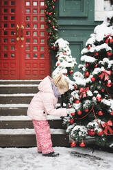 Little girl watching Christmas baubles at Christmas tree outdoors - EYAF00738
