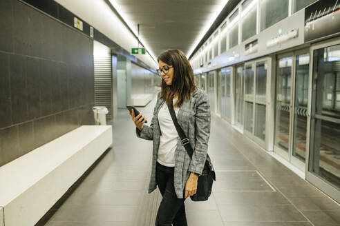 Young businesswoman using the phone at the subway station, waiting for the train - JRFF03898