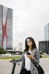 Young businesswoman using smartphone standing on e-scooter in the city - JRFF03904