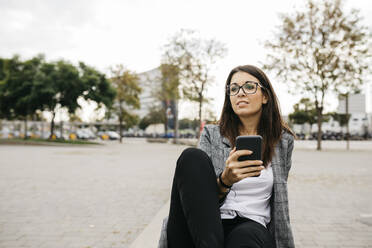 Young businesswoman using smartphone, sitting on bench in the city - JRFF03910