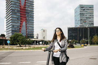 Young businesswoman with e-scooter in the city - JRFF03913