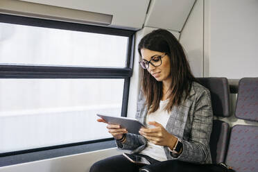 Brunette woman while traveling by train to work, with a tablet in her hands - JRFF03928