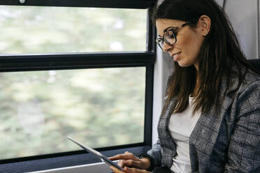 Brunette woman while traveling by train to work, with a tablet in her hands - JRFF03931