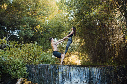 Couple practicing acro yoga together on a waterfall - MIMFF00006