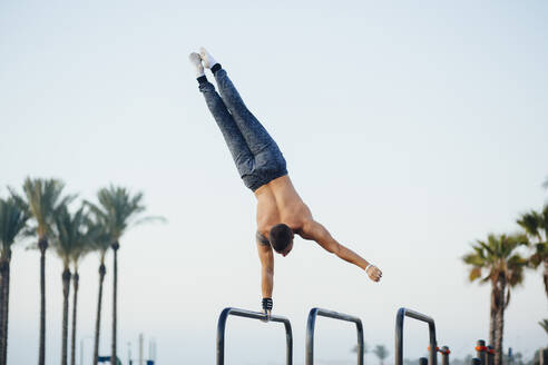 Young man practicing calisthenics at an outdoor gym - MIMFF00018