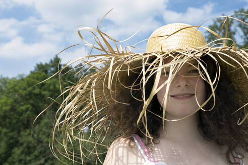 Portrait of smiling young woman wearing frayed straw hat in nature - PSTF00495