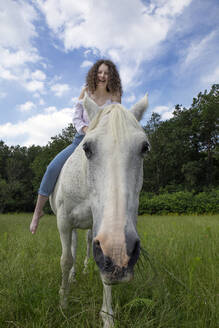 Portrait of grazing horse with laughing rider on back - PSTF00519