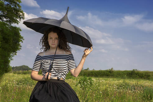 Portrait of young woman with umbrella on a meadow - PSTF00549