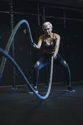 Blond sportswoman having workout with ropes - MADF01439