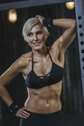 Portrait of blond sportswoman wearing black sports bra in gym - MADF01442