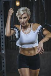 Portrait of blond sportswoman wearing white t-shirt in gym - MADF01445