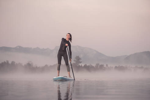 Woman stand up paddling on lake Kirchsee at morning mist, Bad Toelz, Bavaria, Germany - WFF00197