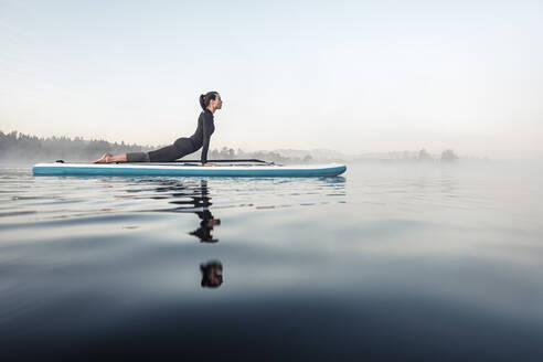 Woman practicing paddle board yoga on lake Kirchsee in the morning, Bad Toelz, Bavaria, Germany - WFF00200