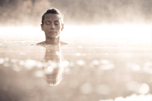 Woman bathing in a lake at morning mist - WFF00212
