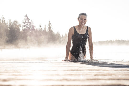 Happy woman wearing black swimsuit bathing in a lake at morning mist - WFF00215