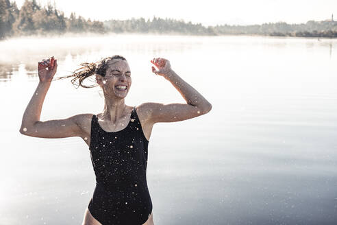 Cheerful woman wearing black swimsuit at a lake at morning mist - WFF00218