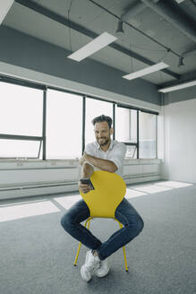 Portrait of confident mature businessman sitting on yellow chair in empty office - KNSF06896