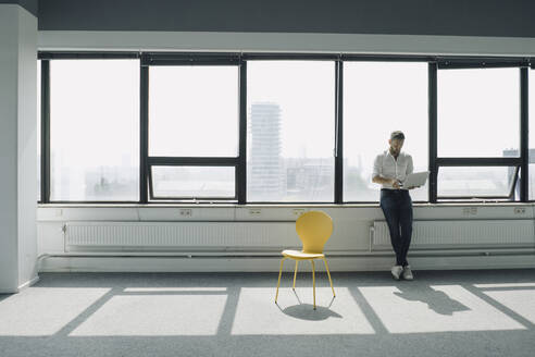 Mature businessman using laptop at the window in empty office - KNSF06911