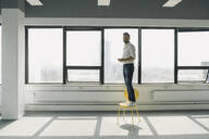 Happy mature businessman standing on yellow chair in empty office - KNSF06914