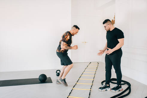 Fitness instructor observing man using agility ladder in studio - ISF23186