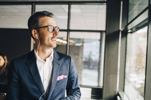 Smiling businessman wearing headphones looking away in office - MASF15067
