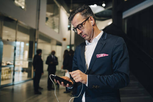 Businessman using smart phone while listening through headphones in office - MASF15106