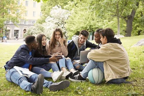 Smiling teenage boy showing smart phone to friends while sitting at park - MASF15139