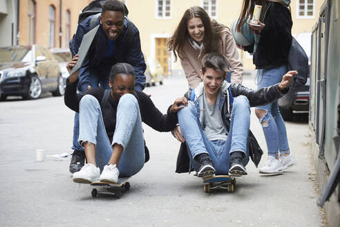 Cheerful friends pushing teenagers sitting on skateboard - MASF15160