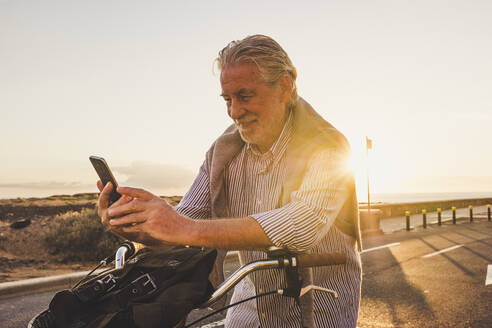 Senior man using smartphone on bicycle at sunset, Tenerife - SIPF02088