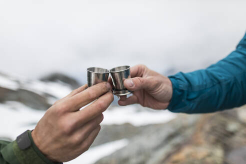 Detail of two men toasting shot glasses in the mountains. - CAVF69993