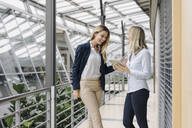 Two happy young businesswomen with tablet talking in modern office building - JOSF03824