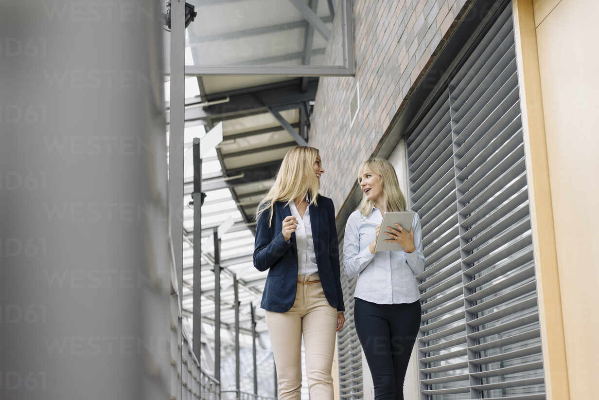 Two young businesswomen with tablet walking and talking in modern office building - JOSF03827 - Joseffson/Westend61