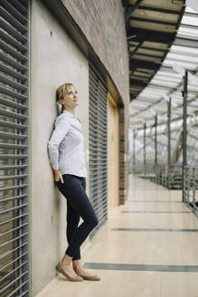 Young businesswoman leaning against a wall in a modern office building - JOSF03830