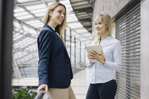 Two happy young businesswomen with tablet in modern office building - JOSF03833