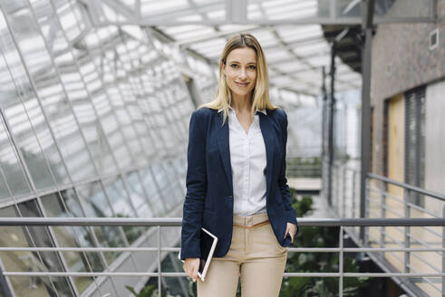Portrait of a smiling young businesswoman in a modern office building - JOSF03836
