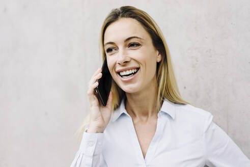 Portrait of a happy young businesswoman on the phone - JOSF03845